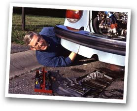 Dr. Berg works on his V W bug, Herbie.